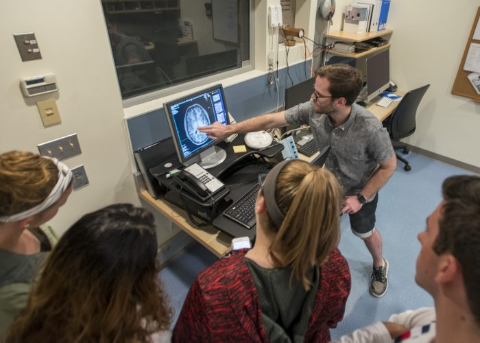 Photo of Charles Davis, a graduate student in psychology shows an axial image of the brain to a group of EO Smith high school on May 17, 2019. (Sean Flynn/UConn Photo)